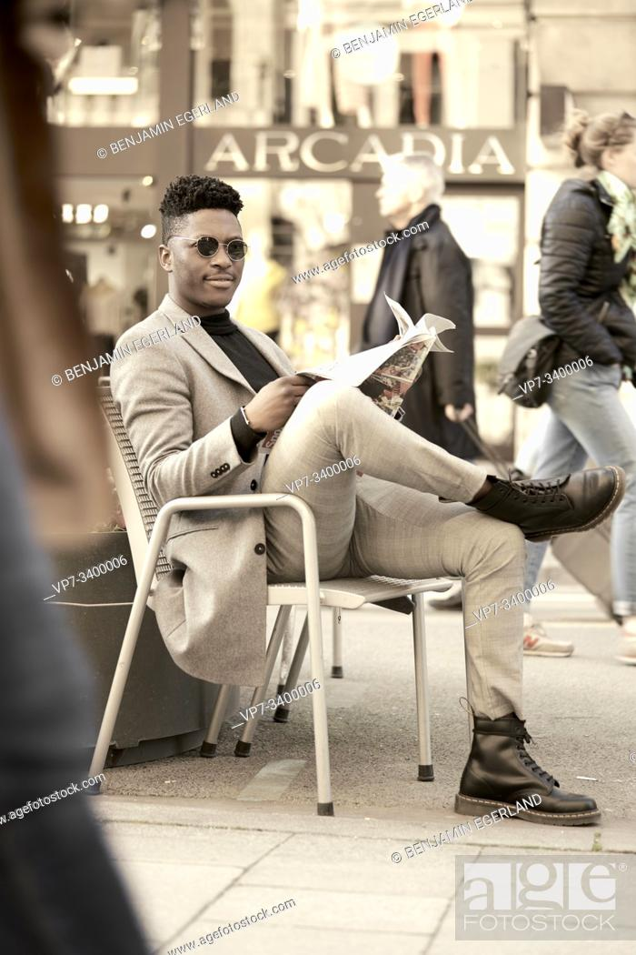 Stock Photo: Young African man sitting on chair, reading newspaper, in Munich, Germany.