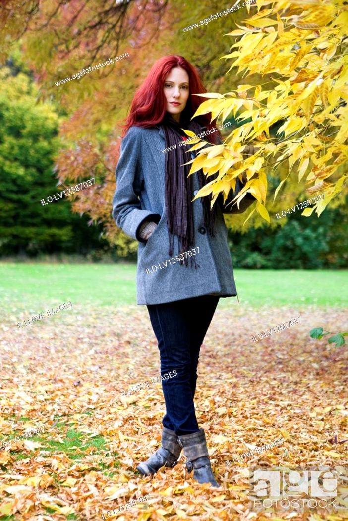 Stock Photo: A young woman standing next to a tree in autumn time.