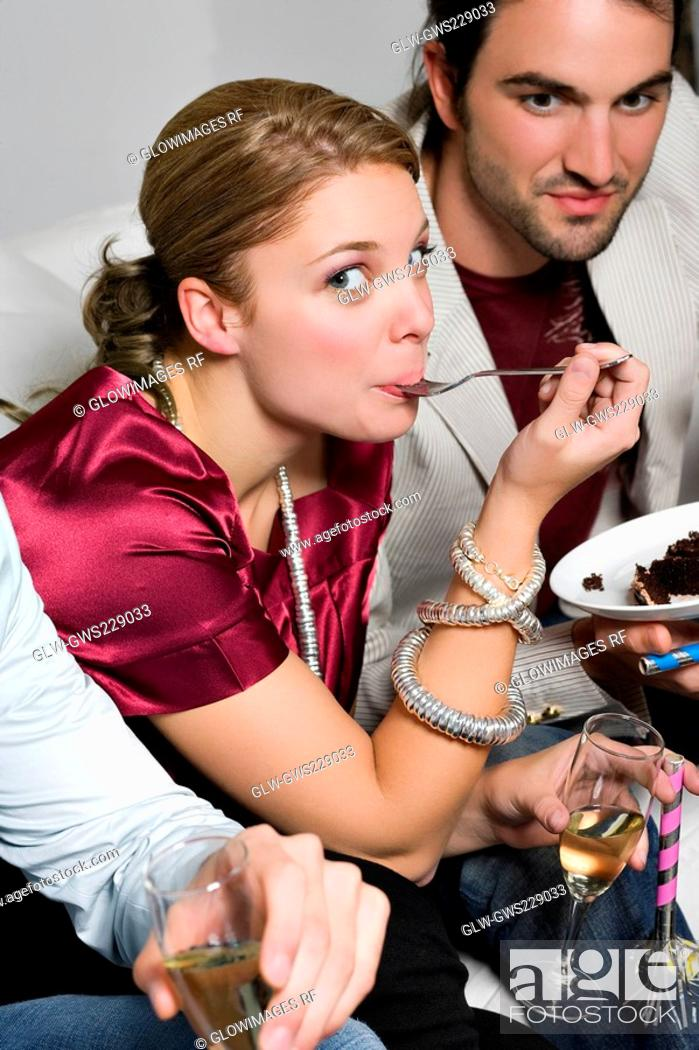 Stock Photo: Portrait of a young woman eating cake and sitting with her friends.