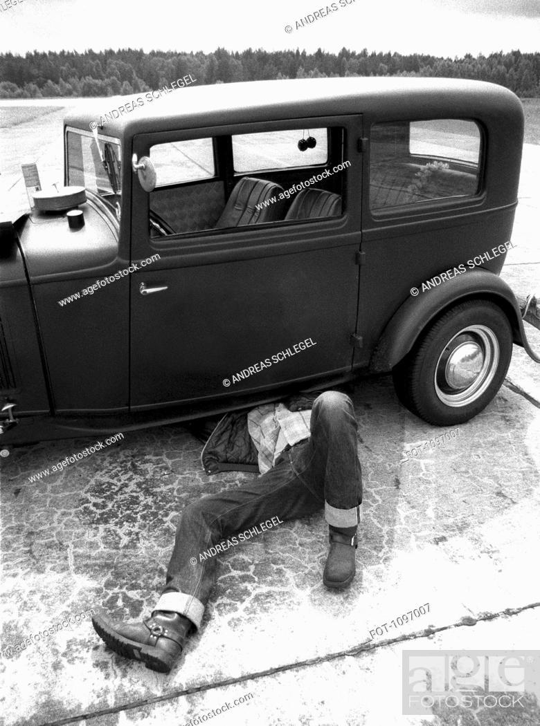 Stock Photo: A man repairing an old car.