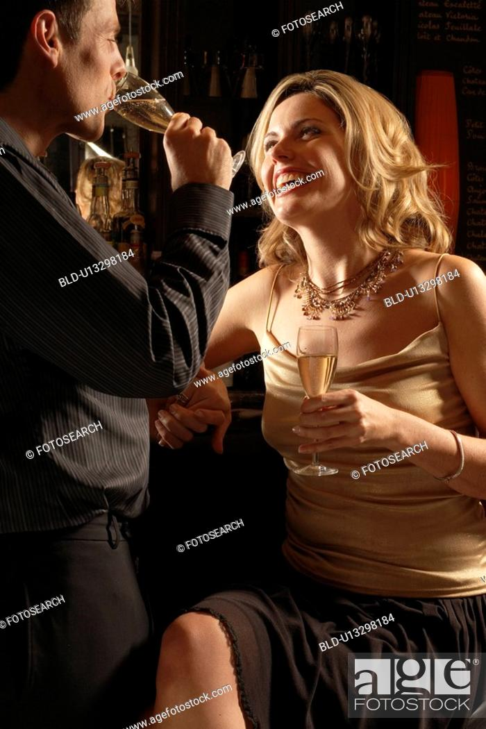 Stock Photo: Mid adult couple drinking champagne at bar.