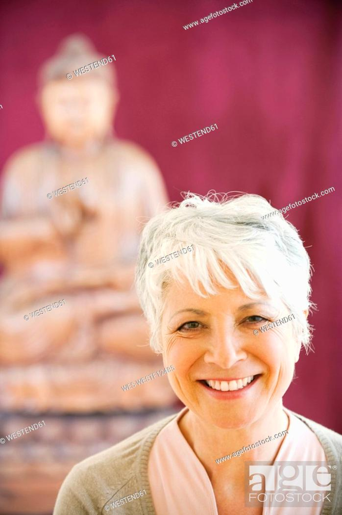 Stock Photo: Portrait of a senior woman in background a buddha statue.