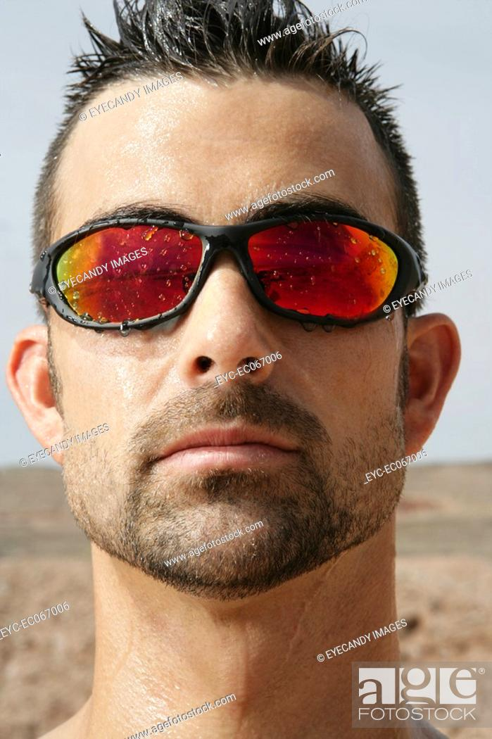 Stock Photo: Portrait of man outside wearing reflective sunglasses.