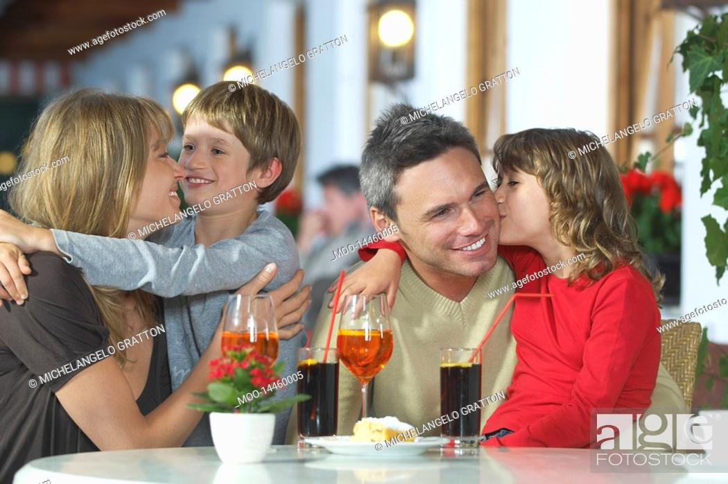 Stock Photo: Parents and children 7-9 with drinks embracing at restaurant.