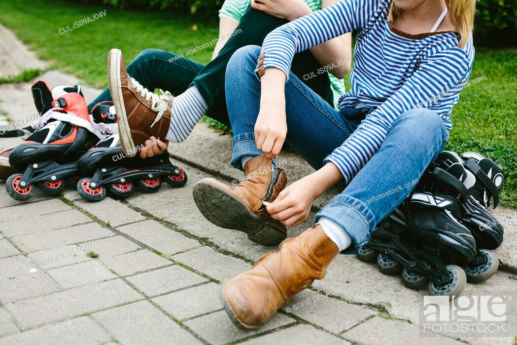 Stock Photo: Two sisters sitting on sidewalk unzipping boots for rollerblades.