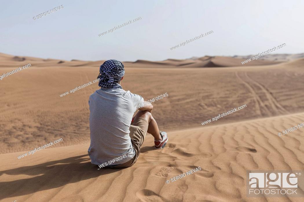 Stock Photo: Male tourist sitting on sand dunes in desert at Dubai, United Arab Emirates.