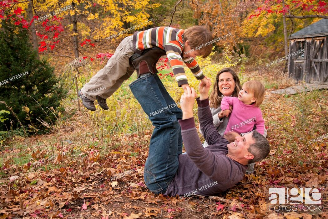 Stock Photo: Nuclear family with parents in their 30s and with a 3 year old boy and a one year old girl playing on leaf covered lawn in fall.