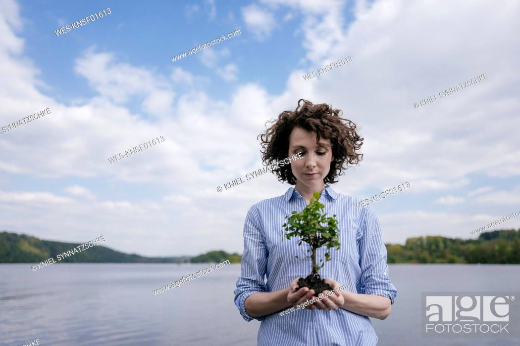 Stock Photo: Woman at lake holding little tree in her hands.