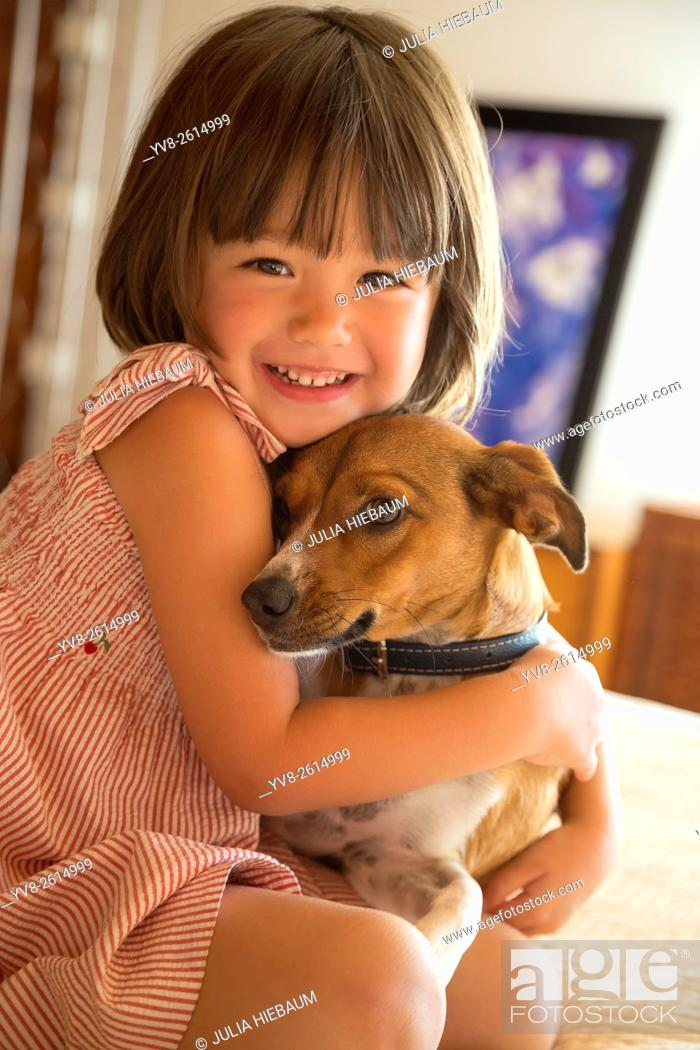 Stock Photo: Toddler girl embracing her dog at home.