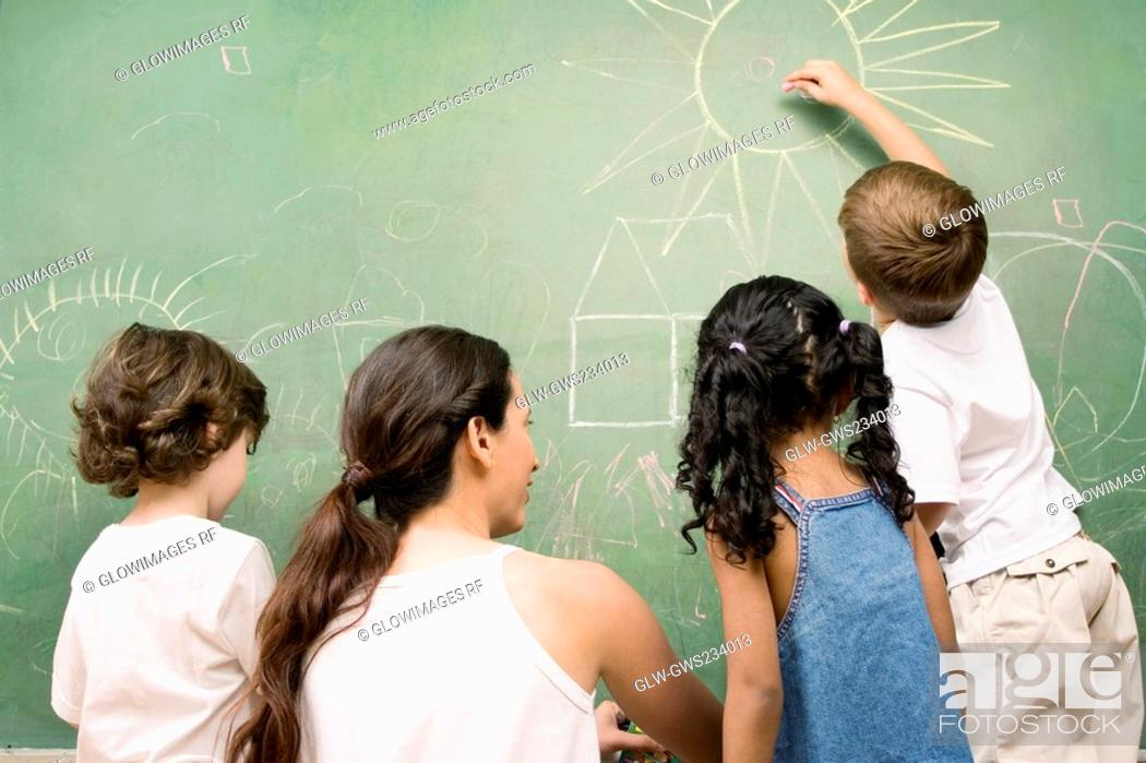 Stock Photo: Rear view of a female teacher teaching her students.