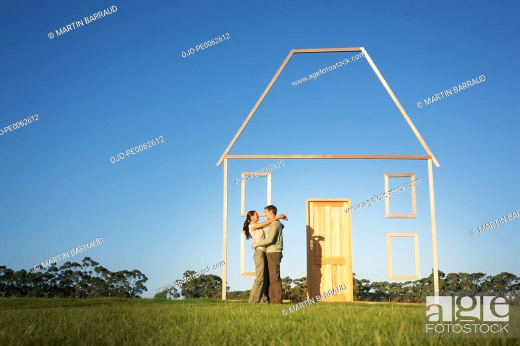 Stock Photo: Couple hugging next to vertical house outline.