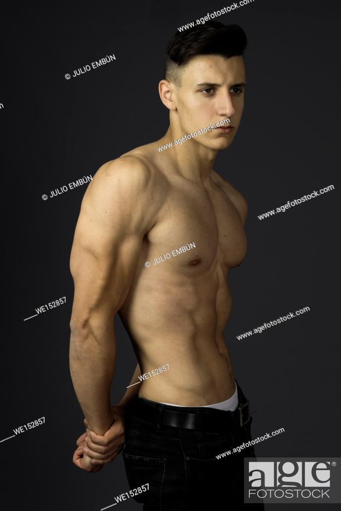 Photo de stock: Young guy in jeans and shirtless poses in the studio.