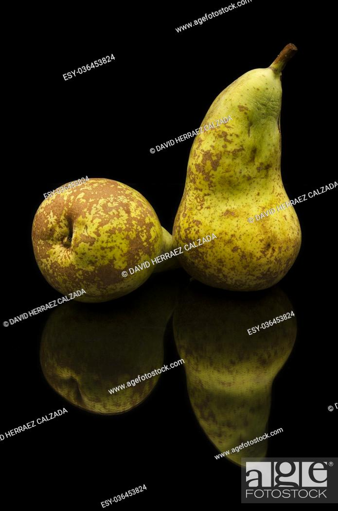 Stock Photo: Brown pears on black isolated background.