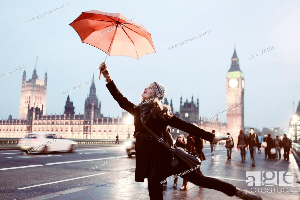 Stock Photo: Woman with umbrella and view of the Houses of Parliament and Westminster Bridge, London, England.