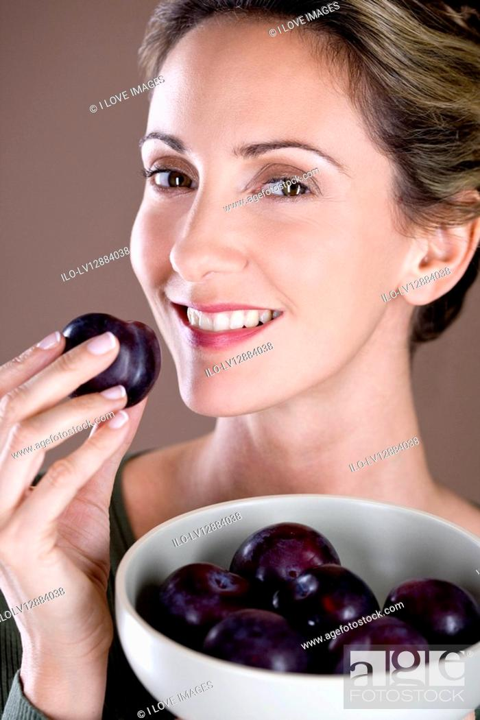 Stock Photo: A mid adult woman eating a plum.