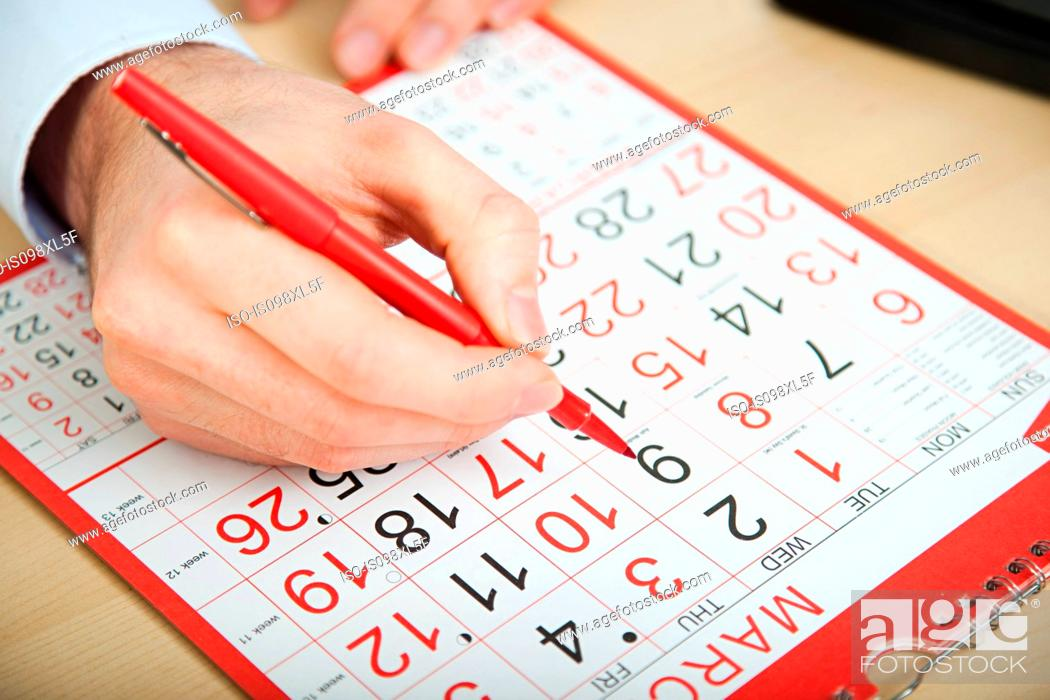 Stock Photo: Office worker marking calendar with red pen.