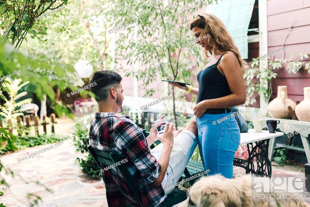 Stock Photo: Young couple and their dog sitting smiling in the garden chairs near their wooden house.