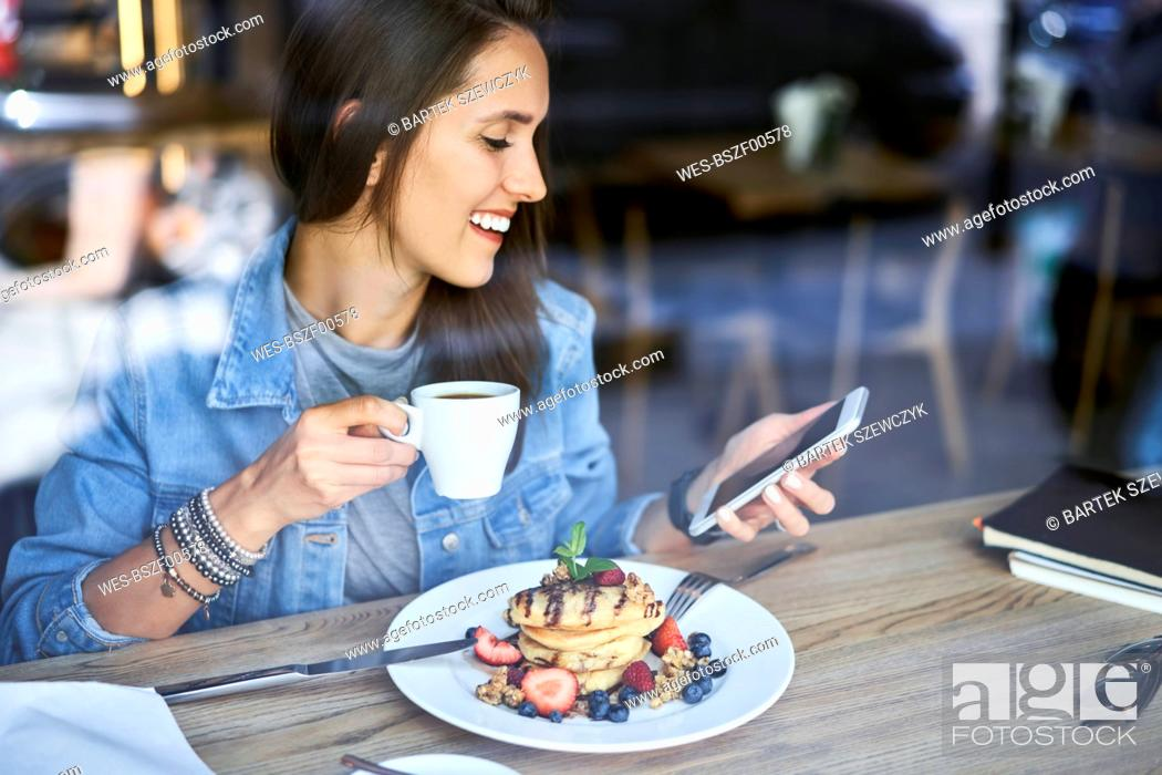 Photo de stock: Smiling young woman with plate of pancakes using phone in cafe.
