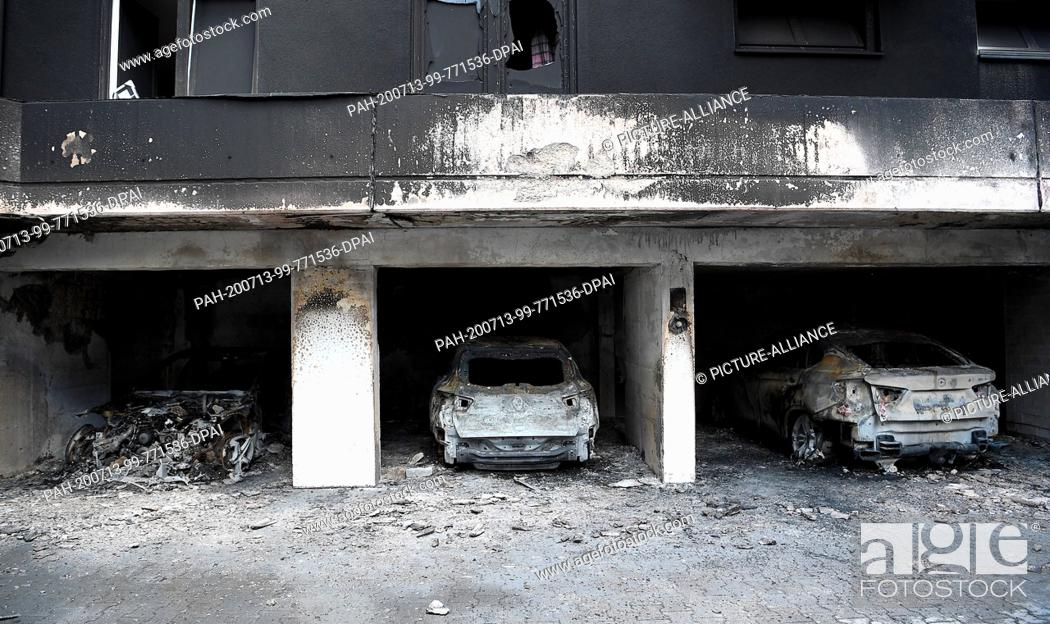 Stock Photo: 13 July 2020, Berlin: Burnt-out vehicles are parked in a garage in the Neukölln district. Six cars had burned down during the night.