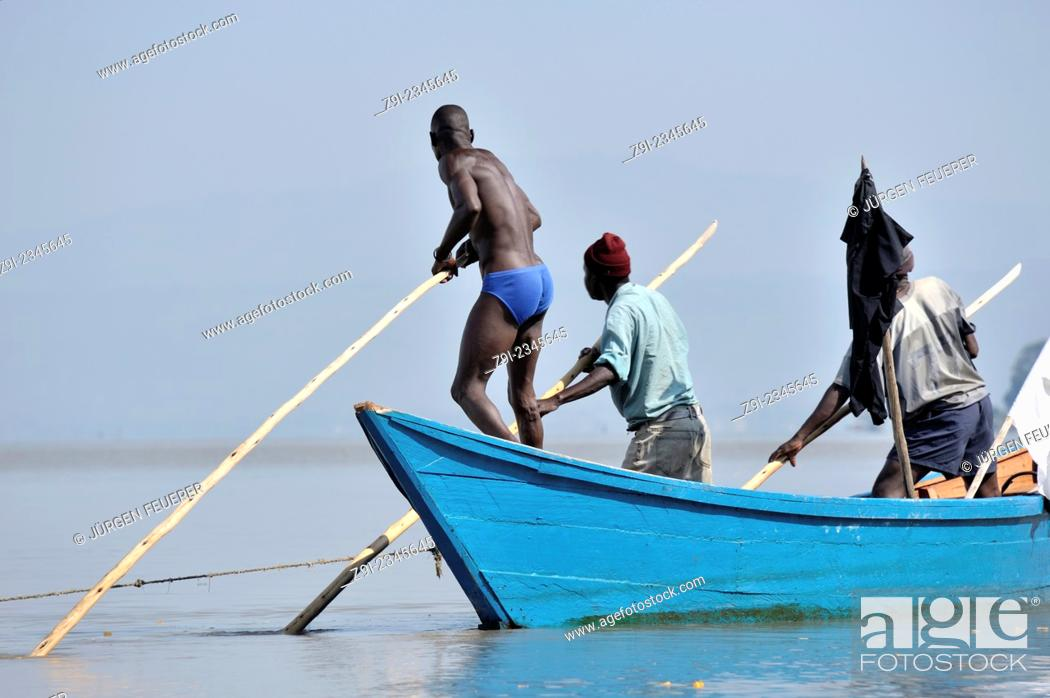 Stock Photo: Fishers pushing their boat through the water at Lake Victoria, Kenya.