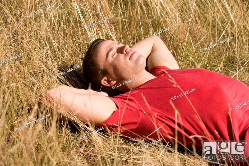 Stock Photo: A young man lying in the sun.