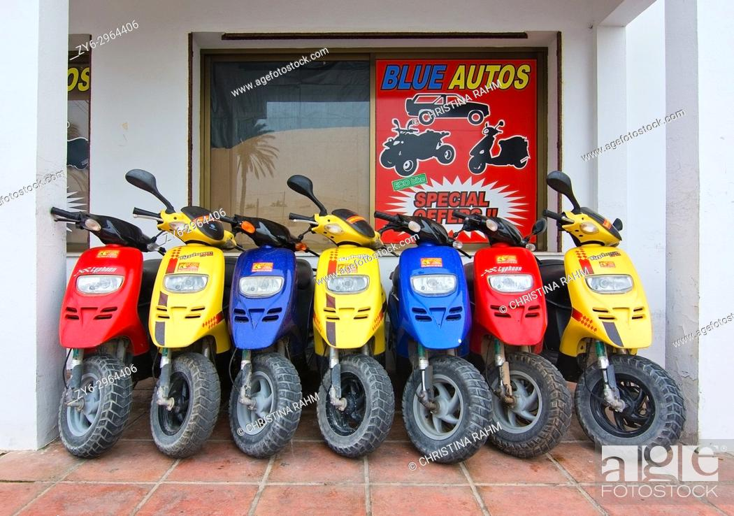 Stock Photo: Seven scooters in blue, yellow and red colors packed together in Formentera, Balearic islands, Spain.