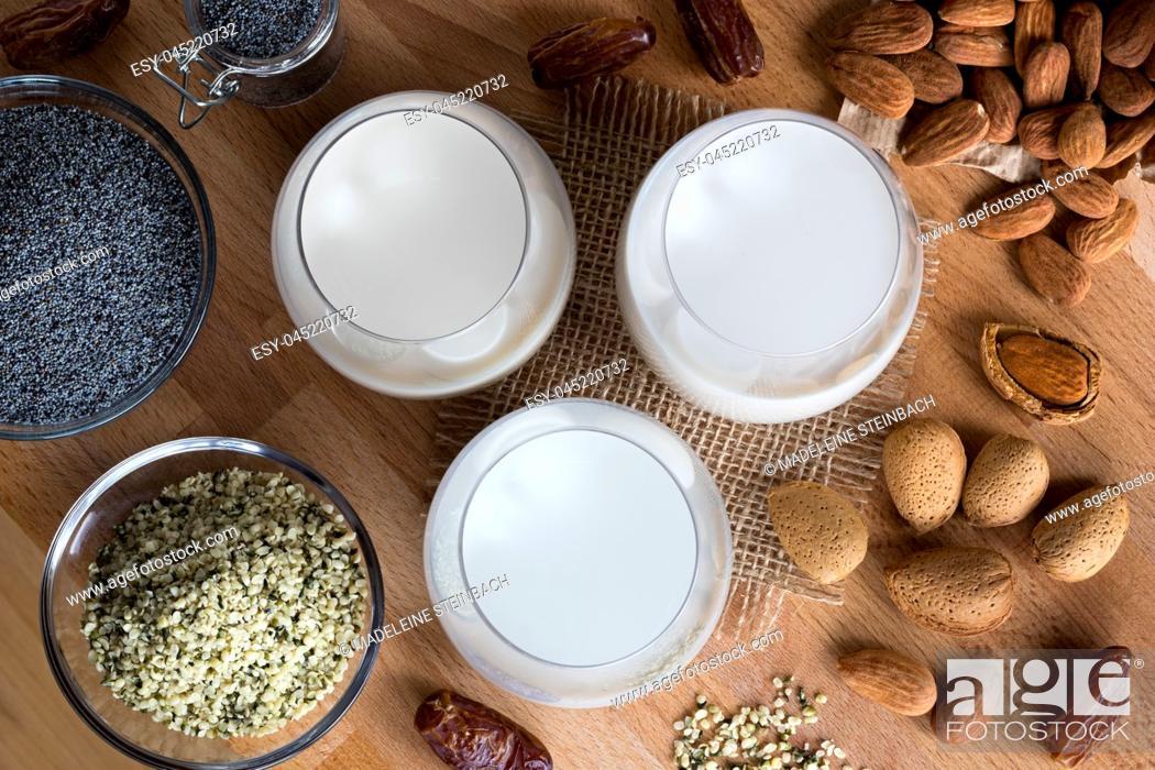 Stock Photo: Top view of three glasses of vegan plant milk - almond milk, poppy seed milk and hemp seed milk, with shelled and unshelled almonds, poppy seeds.