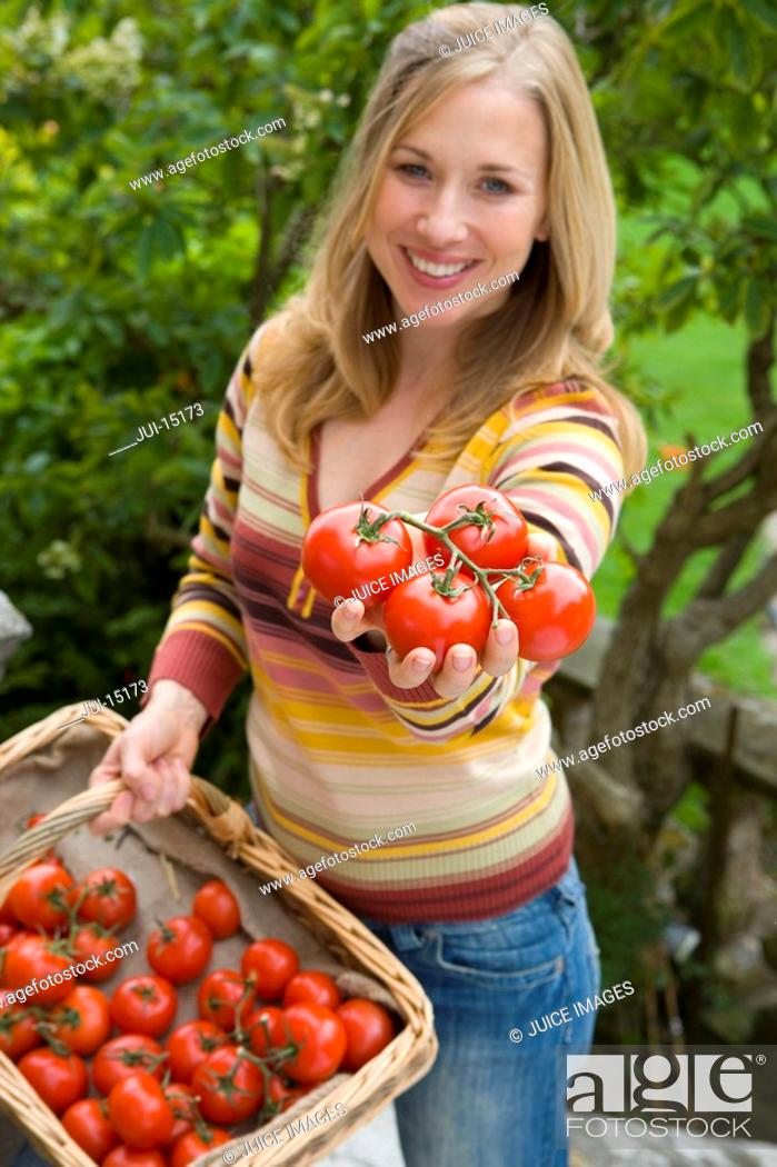 Stock Photo: Woman with basket of tomatoes, smiling, portrait.