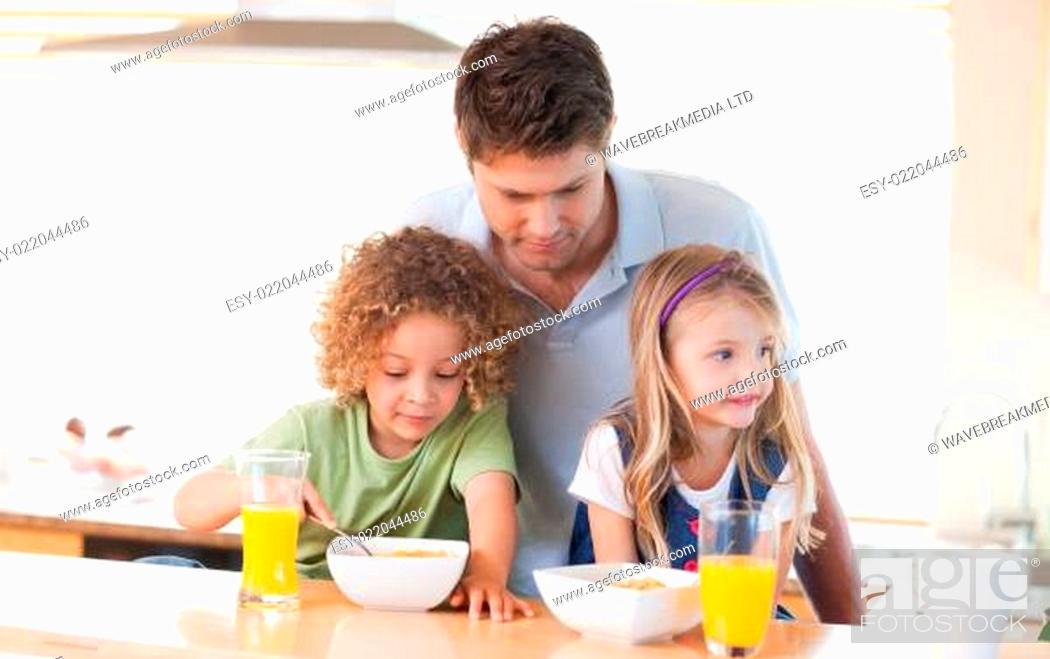 Stock Photo: Young father with his children having breakfast.