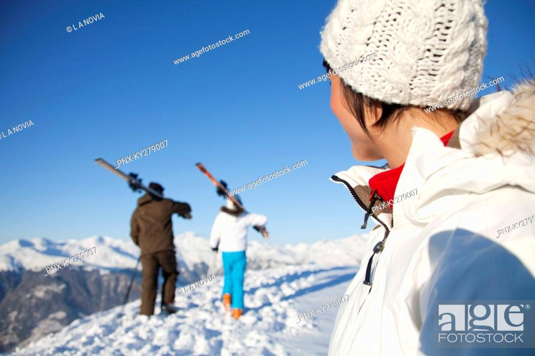 Stock Photo: Woman looking at father and daughter carrying skis.