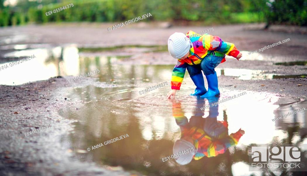 Stock Photo: Child walking in wellies and jumping in puddle on rainy weather. Boy under rain in summer outdoors.