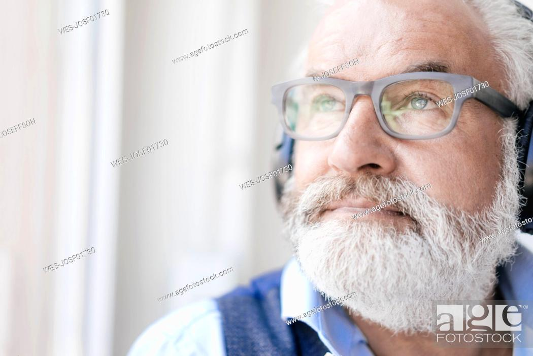 Stock Photo: Mature man wearing glasses and headphones at the window.