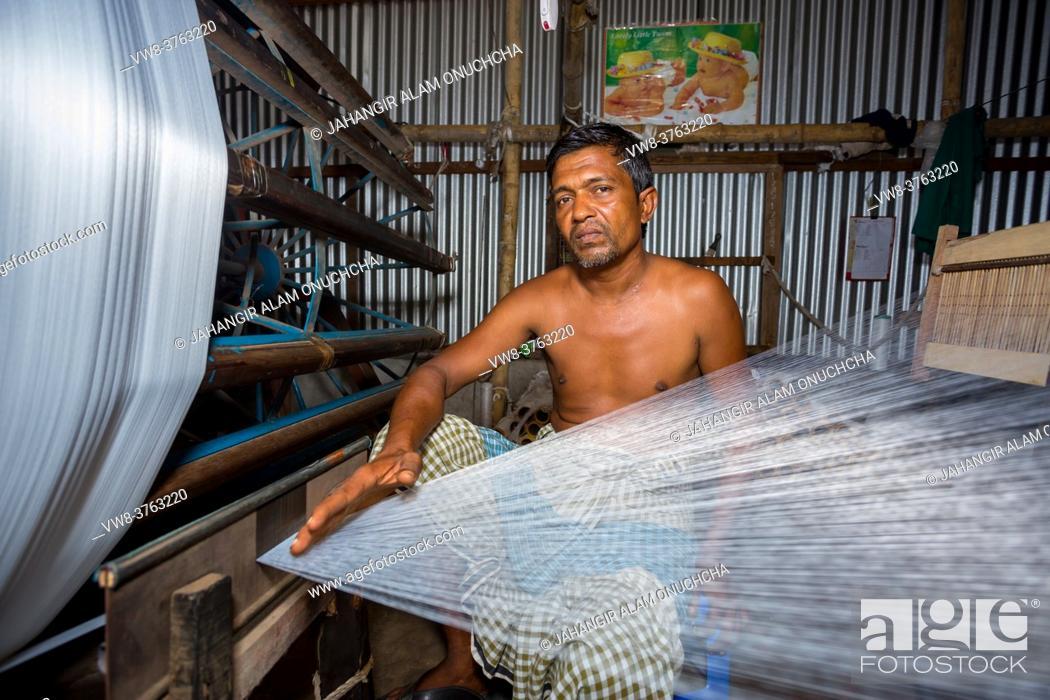 Stock Photo: A factory worker makes white yarn spools for making clothes at Narsingdi, Bangladesh.