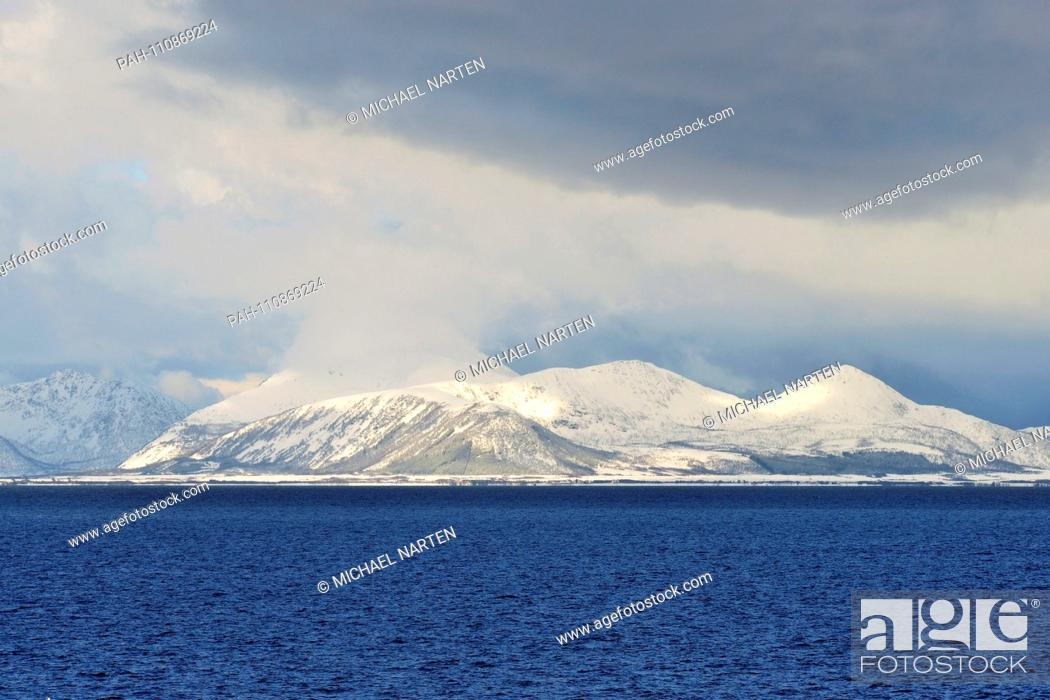 Stock Photo: Dark clouds above the snowcapped coast from the Vesterålen Island Andøya with the blue water of the Andfjord in the forefront, 10 March 2017 | usage worldwide.