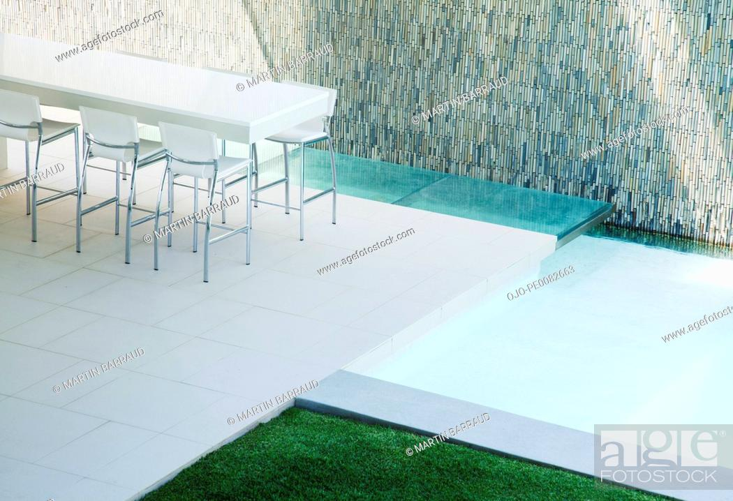 Stock Photo: Barstools around counter on patio with swimming pool.