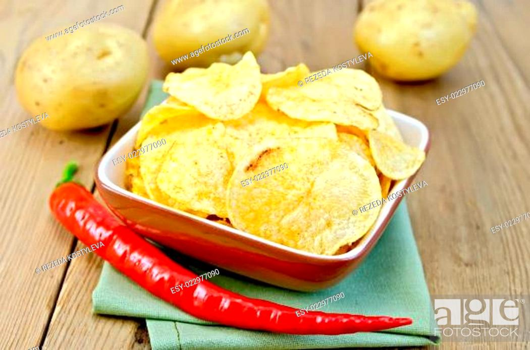Stock Photo: Chips in a bowl with hot peppers and potatoes on board.
