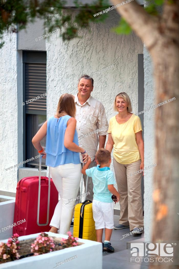 Stock Photo: Young mother and little son coming to visit grandparents. Happy man and woman meeting daughter and grandson by the house.