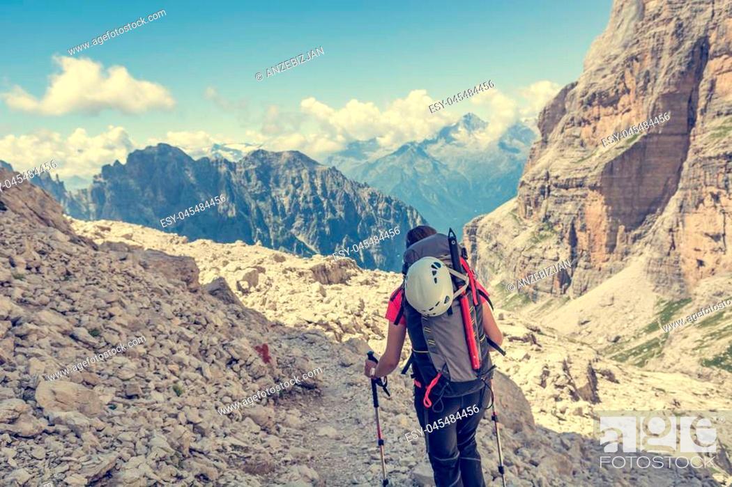 Stock Photo: Female trekker walking along mountain valley. Trekking Brenta Dolomites, Sentiero delle Bocchette Alte.