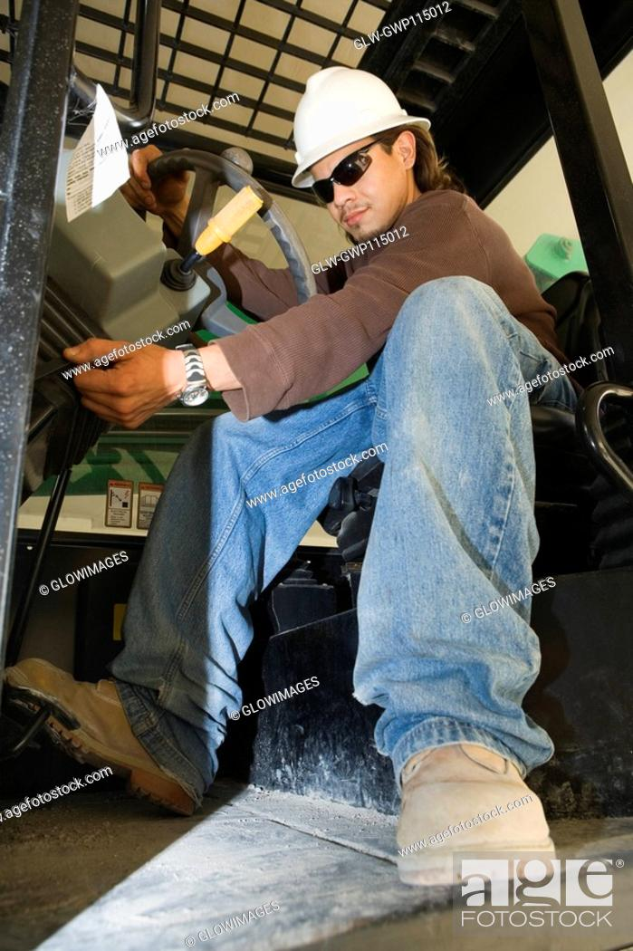 Stock Photo: Low angle view of a young man operating a crane.