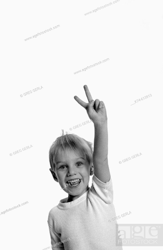 Stock Photo: image of young boy making a peace sign with his fingers.