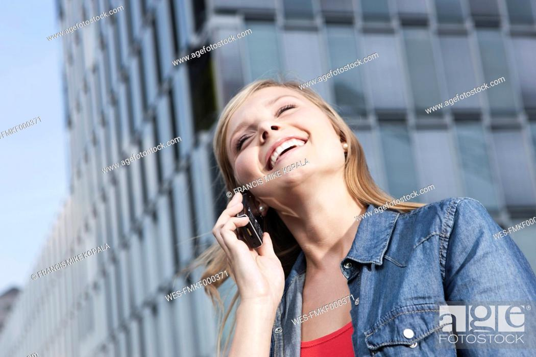 Stock Photo: Germany, Cologne, Young woman on phone, smiling, portrait.