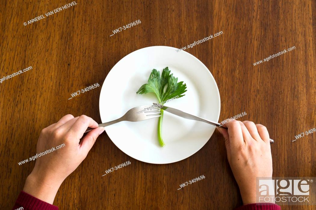Stock Photo: diet concept. one green vegetable on an empty white plate with woman hands celery on wood table healthy top view.