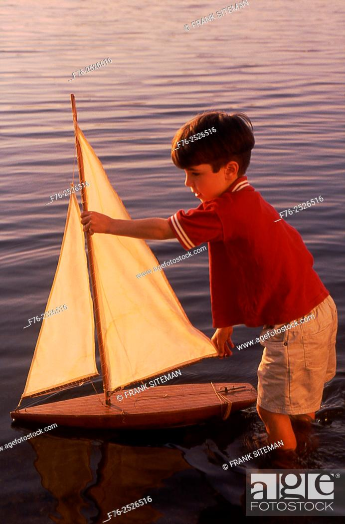 Stock Photo: Boy, standing nearly knee deep in water, playing with toy sailboat in Upper Mystic Lake in Medford, MA, model released mr-5215.