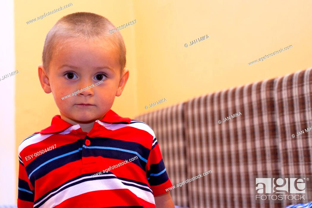 Stock Photo: Portrait of little boy sitting on the bed.