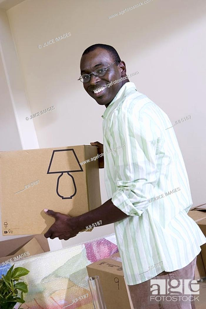 Stock Photo: Man moving house, holding cardboard box in living room, smiling, side view, portrait tilt.