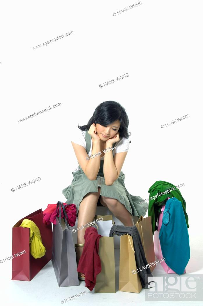 Stock Photo: Woman depressed while looking at clothes near shopping bags.
