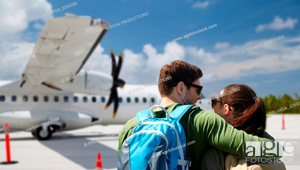 Stock Photo: couple of tourists with backpacks over airplane.