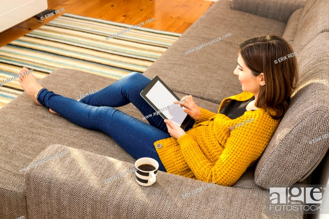 Stock Photo: Beautiful young woman working with a tablet at home.