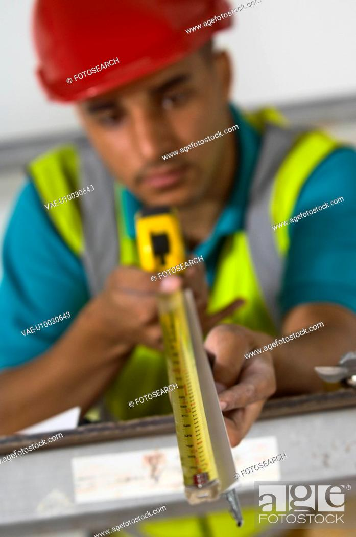 Stock Photo: Builder measuring studs with tape measure.