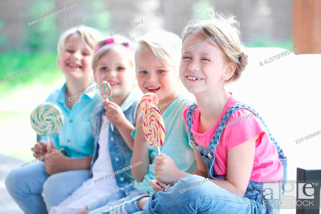 Stock Photo: Group of happy smiling children with lollipops outdoors.